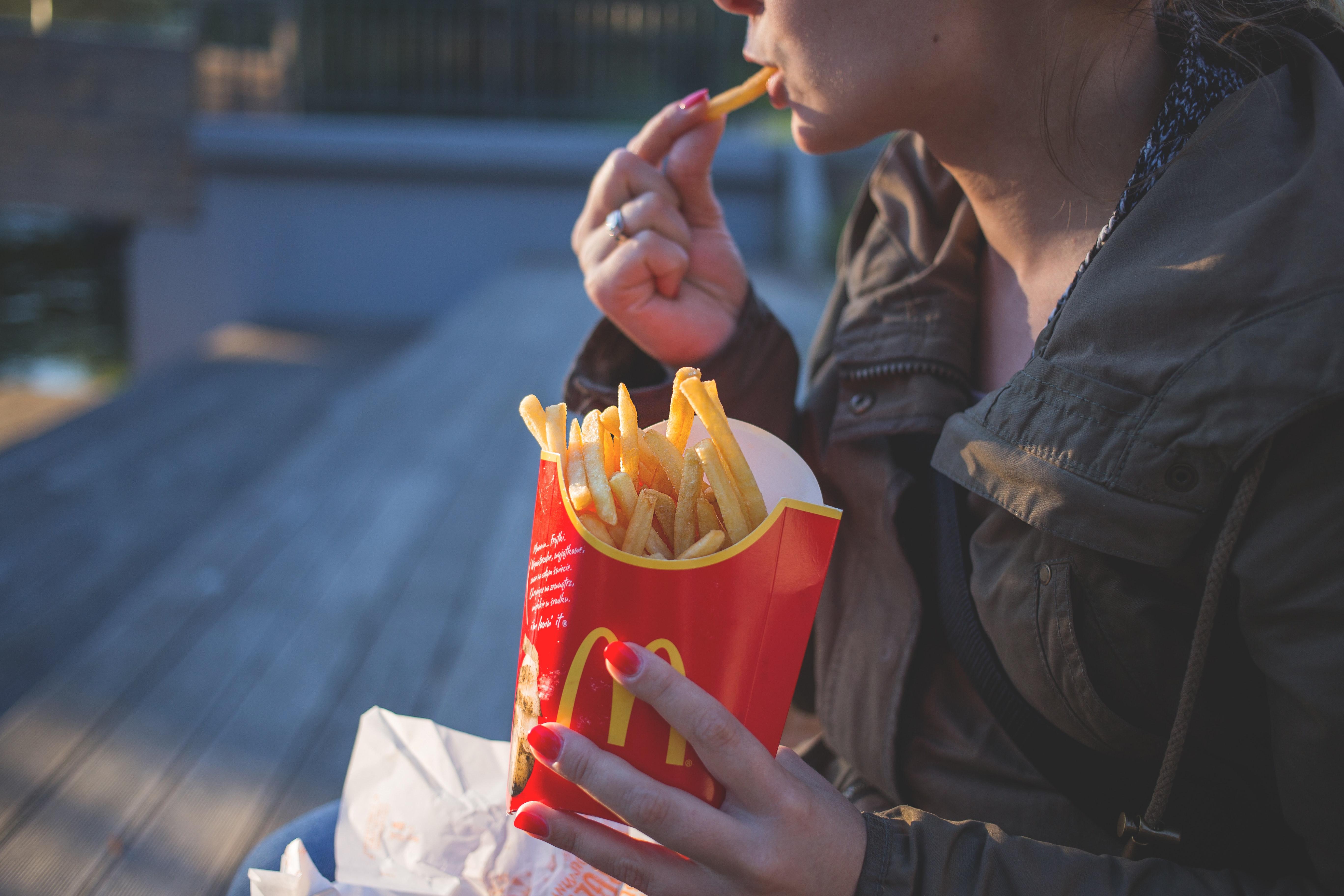 Kvinne som spiser pomme frites